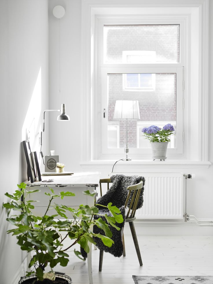 white airy home office. all white office with serene desk and green plants give the perfect touch of color airy home c