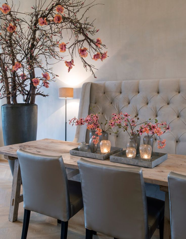 the restaurant feel created by the big plush seat on the wall the large table and chairs the theme of the blossoms repeated from the floor vase to the