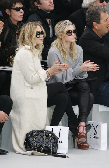 The girls took in the Chanel Fall/Winter 2008 show with killer eyewear. Ashley paired a long, white tweed coat with black ankle boots, a quilted bag, and oversize shades. Mary-Kate went sporty in a gray sweater, black leather leggings, and YSL platforms and a printed headscarf.
