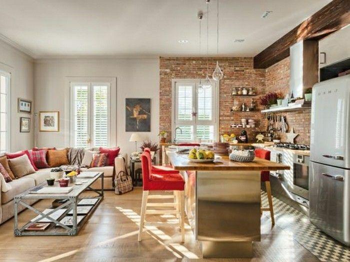 jolie cuisine en briques rouges, sol en parquet clair, canapé d'angle beige