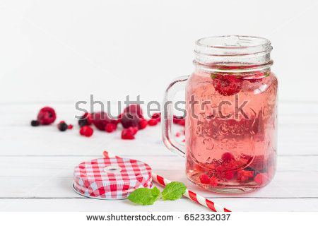 Raspberry healthy lemonade in an opened vintage mason jar with mint leaf and red paper straw placed on a white wooden board. Drink for the holidays.