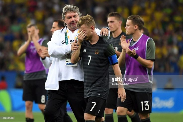 Germany's midfielder Maximilian Meyer (C) is consolled following the Rio 2016 Olympic Games men's football gold medal match between Brazil and Germany at the Maracana stadium in Rio de Janeiro on August 20, 2016. Neymar struck the winning penalty as Brazil claimed a first ever Olympic football gold medal with victory over Germany at the Maracana on Saturday. / AFP / Luis Acosta