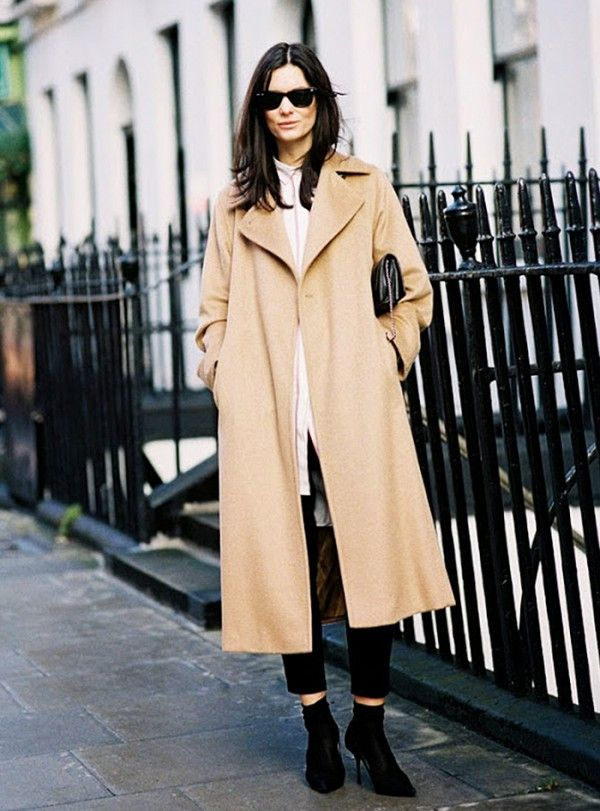 A classic camel coat is paired with black trousers, sleek ankle boots and black sunglasses: