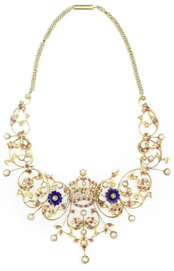 An antique pearl, ruby and enamel necklace, circa 1890. The scrolling openwork necklace centred around a crown between two blue enamel flowerheads, set throughout with circular and oval-cut rubies, half pearls and pearls on knife-edge wires.