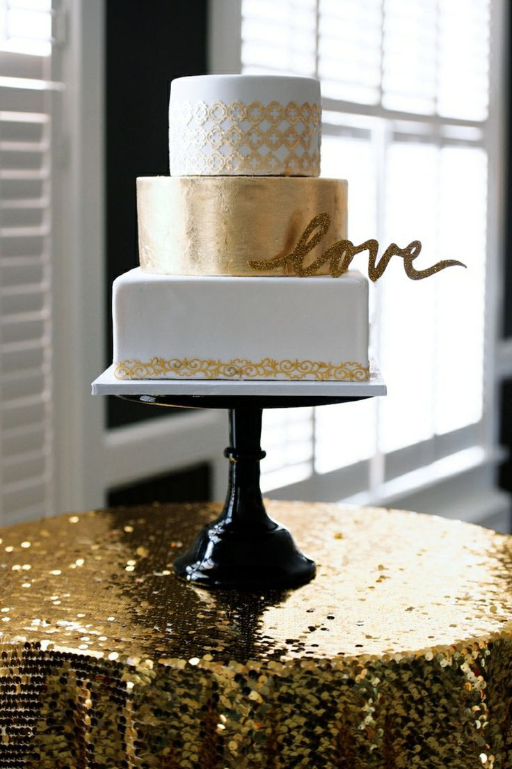Modern white and gold wedding cake with a metallic layer in the middle...that tablecloth is tragic though