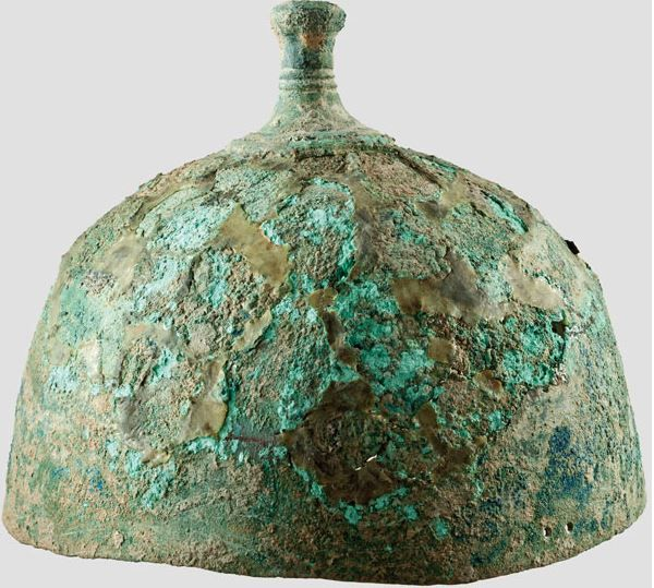 Late Urnfield Period, 10th - 9th century B.C.   A flat knob helmet, hemispherical bronze skull. A solid cast and contoured knob soldered on the crown, with a central perforation to insert the crest. On each side of the lower edge, two perforations to attach the cheek pieces and a helmet band. The circular, lower part of the skull intact, likewise the knob, 21.5 cm high