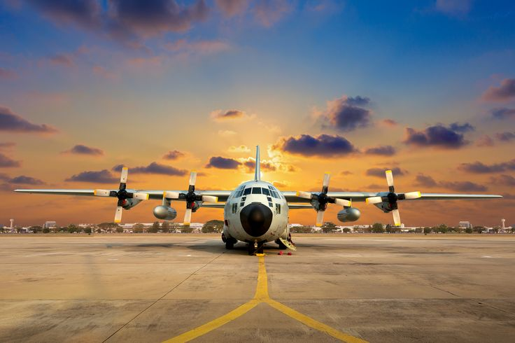 Military aircraft on the runway during sunset. - Military aircraft on the runway during sunset.