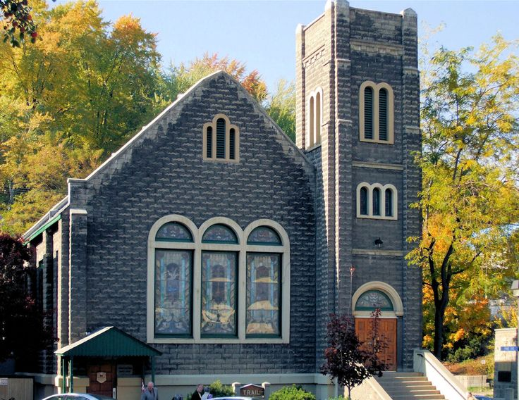 """Stone Church 1:  A small-town United church built of dark grey stone, with square bell tower and stained-glass windows.  Green and yellow autumn foliage and blue sky form the background.  Quarter Page size 1650 x 1275px (300ppi).  Prints at 5.5 x 4.25""""."""