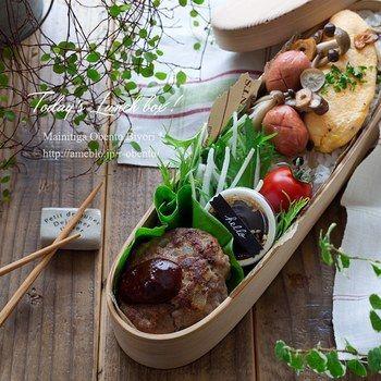 ビジネス用鞄などマチの少ない鞄でも入れやすい、スリム型のお弁当箱。半分にはご飯を詰め、ハンバーグにオムレツなど、おいしそうなおかずが彩り良く並べられています♪大根サラダには別容器に入れたドレッシングがあり、まるでカフェのランチボックスのよう!