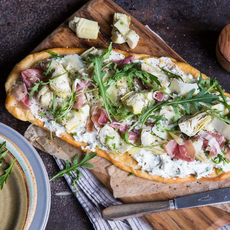 Krosse Pizza mit einem Topping aus Basilikum-Ricotta, Artischockenherzen, Schinken, frisch geriebenem Parmesan und einer frischen Zitronen-Vinaigrette.