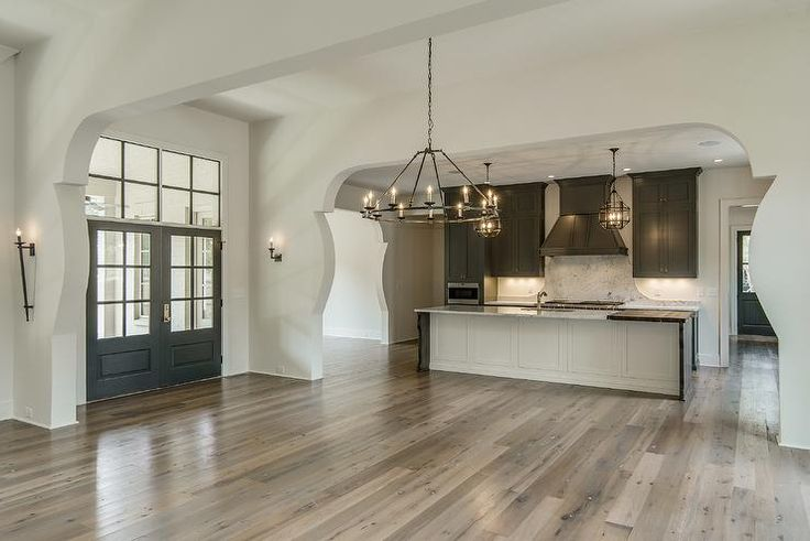 An arched doorway opens to a Mediterranean kitchen filled with gray shaker cabinets adorned with ...