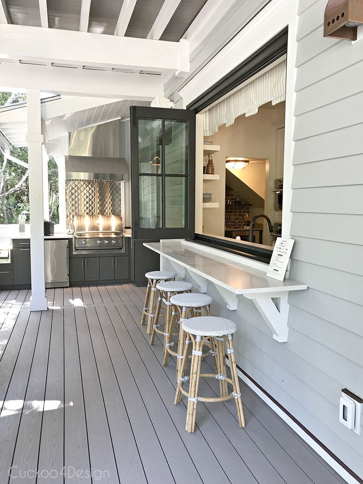 Outdoor bar area that opens into kitchen window with folding door and outdoor kitchen
