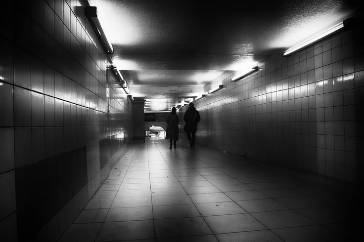 togetherness - A couple walks alone through a lighted long pedestrian tunnel. A play of light and shadow. Black white street photography from Berlin. #street #streetphotography #berlin #street photography