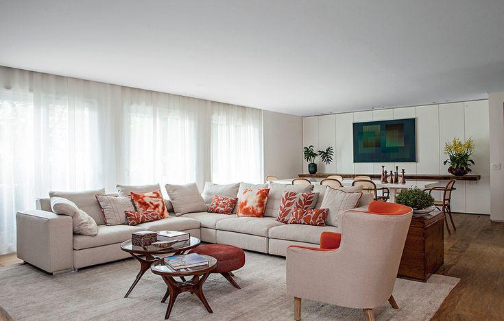 """""""O estar neutro abre-se a pitadas de laranja, seja nas almofadas sobre o sofá italiano, seja no tecido da poltrona. A cor quente combina com o bege. Projeto da designer de interiores Renata Paula"""" No Casa&Jardim"""