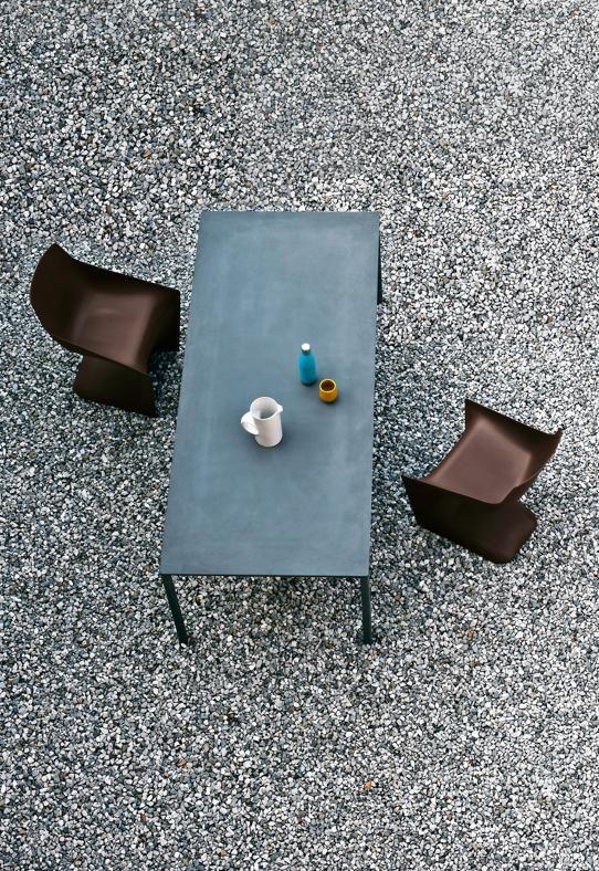Comfort in giardino  KRISTALIA Boiacca, design LucidiPevere. Tavolo con struttura in alluminio verniciato grigio antracite e piano in cemento grigio. Dimensioni cm 200x90. Le sedie impilabili sono Pulp di Christophe Pillet, costituite da una lastra in polipropilene