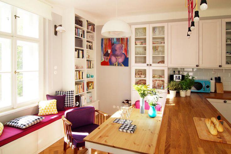Bílé skříňky obohacuje fialové polstrování židle, růžový sedák na lavici s barevnými polštářky, vázičkami nebo šňůrami k žárovkám nad pracovní plochou kuchyně. Černobílé pepito na podlaze odkazuje na historický původ bytu.