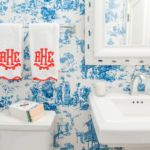 Powder room wallpapered in schumacher chinois china blue wallpaper with custom monogrammed embroidered leontine hand towels. Design Melanie by Design.