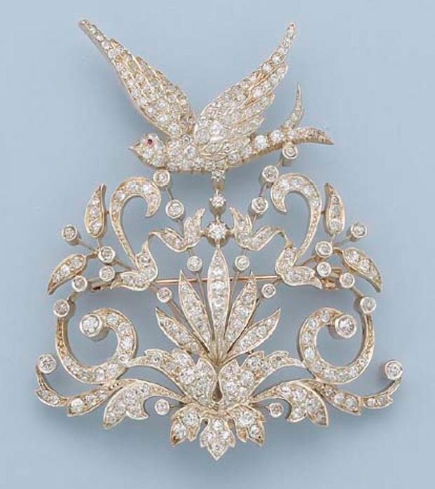 AN ANTIQUE DIAMOND BIRD BROOCH Of openwork collet and scroll design, the old-cut diamond floral motif to the diamond-set bird with ruby eye, mounted in silver and gold, circa 1900, 8.5 cm. high
