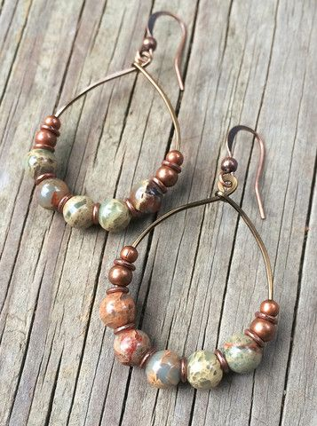 Wire wrapped copper hoop earrings with graduated sizes of antiqued copper beads…