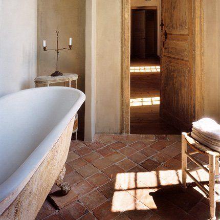 la salle de bains a gardé sa baignoire en fonte émaillée et son sol en tomettes d'origine. Un chandelier Directoire est posé sur un petit meuble Napoléon III.