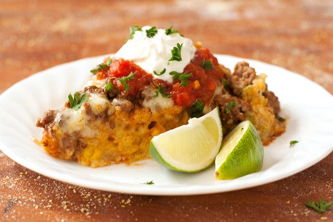 Layers of cornbread, enchilada sauce, spiced ground beef and cheese, baked until melty and topped with all your favorite taco fixings!