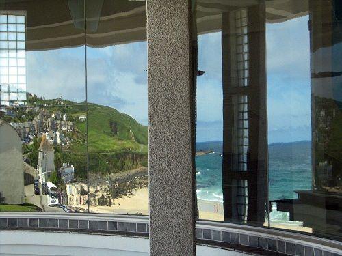 Tate St. Ives, Cornwall  Foto: Ruud Pols  'Het gespiegelde uitzicht via de ronde ramen van het Tate St. Ives in Cornwall, Engeland. Uitzicht op de oceaan, het strand met de eerste badgasten en het dorp op de klif. Weergaloos.'