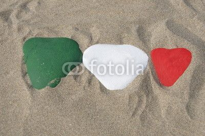 Italian national flag on three hearts of stone over the sand