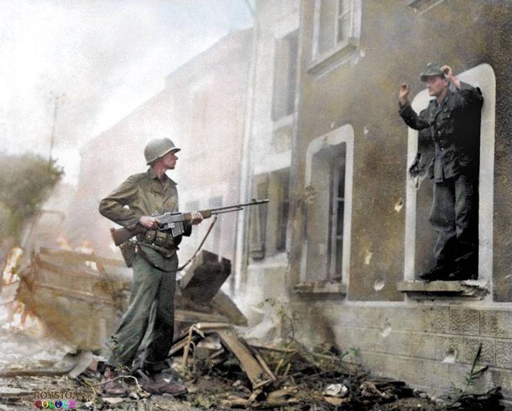 An American infantryman confronts a surrendering German in the town of Illy in the French Ardennes region. September 1944.  He could be with the 28th US Infantry Division, 5th Corps who were in this area on the 7th of September 1944.  In this obviously posed shot, he carries a Browning Automatic Rifle 'BAR' although he is wearing an ammunition belt for the M1 Garand/M1903 Springfield. (Colourised by Royston Leonard UK)