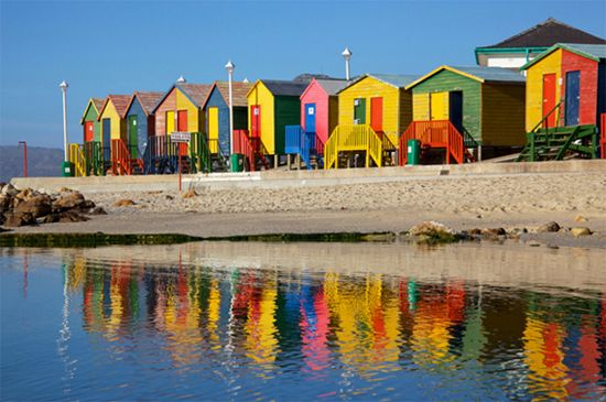 Cape Town, África Bo-Kaap e a praia de Muizenberg. As casinhas pintadas de amarelo, vermelho, verde e azul são usadas para guardar equipamentos de mergulho, pranchas de surf e cadeiras, durante todo o ano.