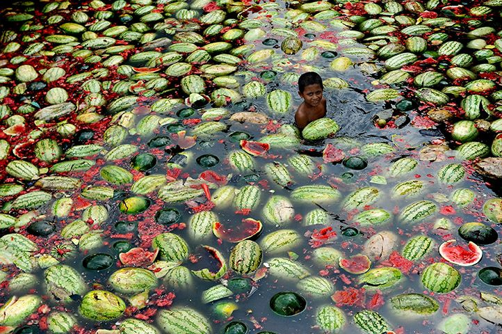 24 hours: Dhaka, Bangladesh: Children gather watermelons from the the water