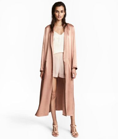 Powder. Long coat in soft satin with a shawl collar, front pockets, a tie belt at waist, and slits at sides. Unlined.