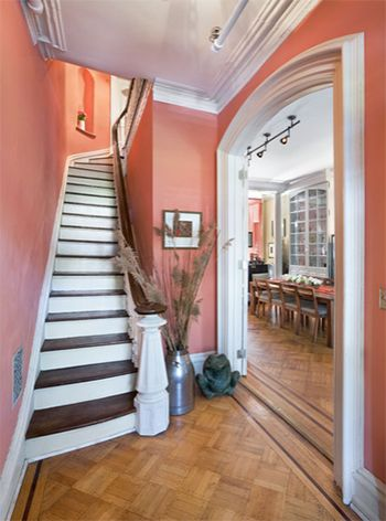 coral reef entry foyer with stair, Sherwin Williams Coral Reef, white trim, coral pink walls, dark stair treads, natural wood floor