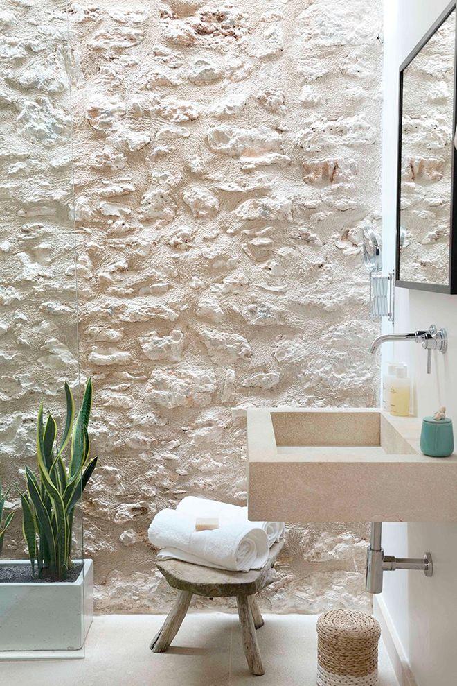 El lujo de lo natural: muro de mampostería de piedra y luz cenital natural en el baño.