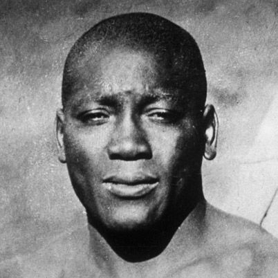 """Born in 1878, Jack Johnson, nicknamed """"Galveston Giant,"""" was the first African American world heavyweight boxing champion. He won the title by knocking out Tommy Burns, and lost it in 1915 to Jess Willard. Discrimination plagued Johnson's career until his fight with Burns. He was arrested for taking his white wife across state lines before being wed. After fighting, he appeared in vaudeville."""