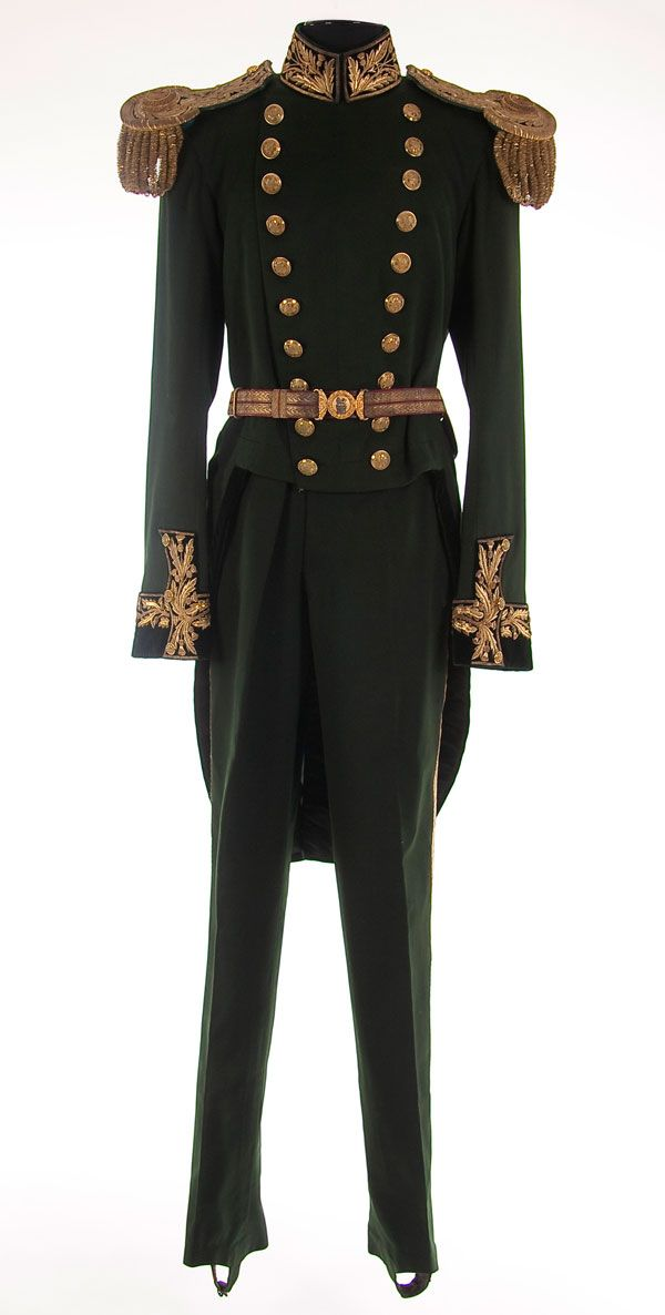 A BRITISH (SCOTTISH) EDWARDIAN UNIFORM OF THE KING'S BODY GUARD OF THE ROYAL COMPANY OF ARCHERS. Dark green wool tail coat with velvet cuffs, collar and facings embroidered in a gold bullion thistle motif, gold King's crown buttons. Displaying a pair of gold and green epaulettes with a Queen's Body Guard unit designation, indicating that the uniform was worn during the transitional period between the two monarchs. Matching green wool trousers with gold braid stripes. Complete with gold…
