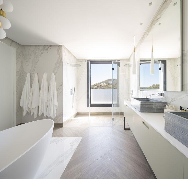 Baño de vivienda en Ibiza, diseñado por Natalia Zubizarreta Interiorismo. Mueble de baño en madera lacada con lavabos sobre encimera mármol gris. Grifería de pared. Espejos retroiluminados. Paredes en azulejo porcelánico gran formato imitación mármol. Baldosa porcelánica imitación madera en espiga. Bañera exenta resina de Kos. Focos integrados en techo. Foseado perimetral en techo retroiluminado. Luminarias suspendidas en dorado y blanco. Ducha doble de obra a medida. Mampara a medida.