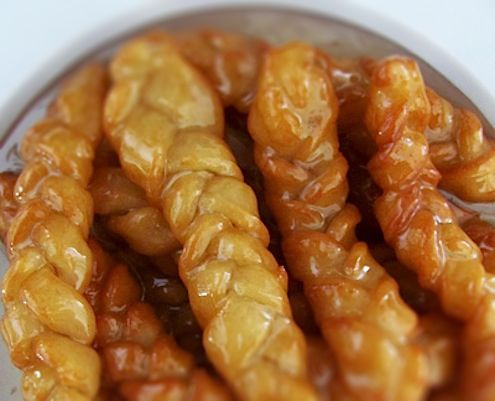 Keoksustrs, a South African classic of plaited, deep-fried dough, soaked in a vanilla sugar syrup.