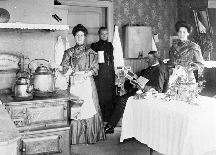 I köket på Wilanders Café i Rödboharen, Norrsundet. Hustrun Sofia med vit kanna i handen, Jöns Wilander sittande. De två kvinnorna med förkläden bör vara anställda i caféet, men deras namn är okända.