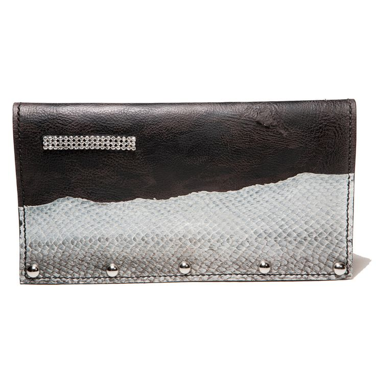 Black studded evening leather clutch with salmon fishleather decoration. With the snowscape like form of the salmon fish leather, this clutch is an artwork by it self and can as well hang on a wall as a decoration as be used to enhance a beauty at a festive event.