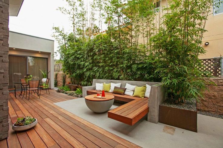 This contemporary patio offers a dining area and a separate lounging area delineated by concrete flooring. A wall of bamboo offers privacy.