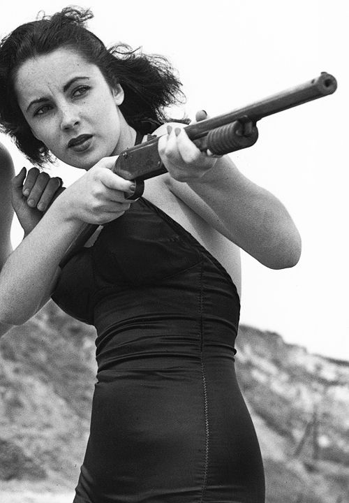 Elizabeth Taylor with a gun on the beach, circa 1949. She is accompanied by her fiance, Conrad Hilton, Jr., aka Nicky Hilton. (Photo by Archive Photos/Getty Images)