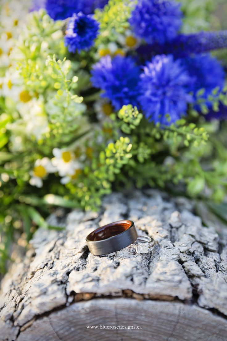 Beautiful ring shot with spring wildflower bouquet. #BlueRoseDesigns #wedding #weddinginspiration #weddingrings #rings #woodring #woodenring #weddingphotography #springbouquet #ringshot #sunset #weddingideas #windsorweddings #windsoressex #sprucewood #sprucewoodshores #windsorweddingphotographer
