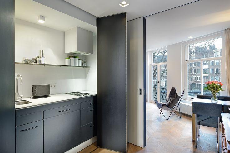 In dit kleine appartement aan de grachtengordel in Amsterdam werd een compacte keuken verdekt opgesteld achter geheel te openen vouwdeuren. De keuken verdwijnt uit het zicht wanneer deze niet wordt gebruikt. Dit geeft een ruim, rustig en opgeruimd beeld in een relatief kleine ruimte. Ontwerp door BNLA architecten uit Amsterdam. Fotografie Studio de Nooyer.