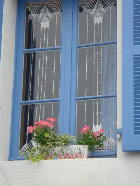 SAINT SULIAC : Des rideaux au crochet qui embellissent joliment les fenêtres bleues