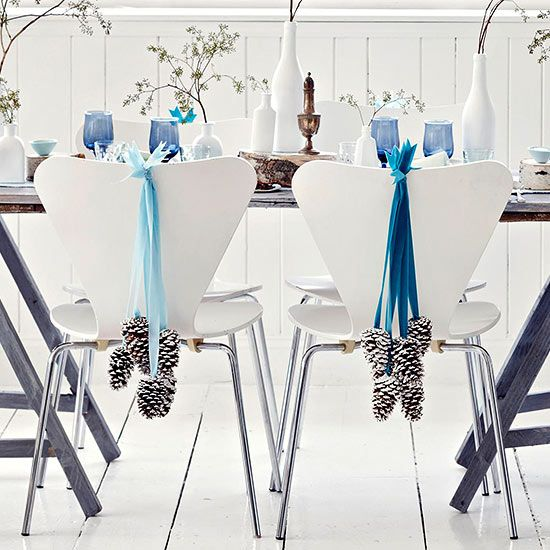 Bring the beauty of a wintry landscape into your home with pinecones and a blue, silver, and white palette. Brush white paint on the tips of pinecones, glue them to velvet ribbon, and secure to the backs of your dining room chairs with adhesive plastic hooks. Budget project price: $7/