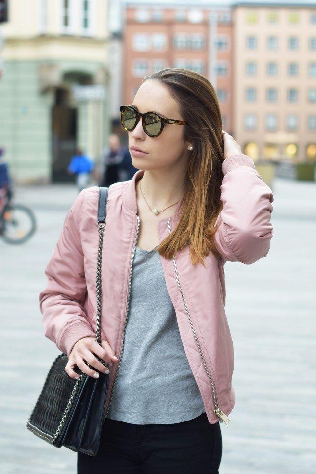 Lässiges Outfit mit rosa Bomberjacke, grauem Shirt und schwarzer Röhrenjeans