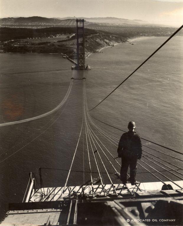 golden gate bridge; A bridge worker stands atop the north (Marin) tower, September, 1935.