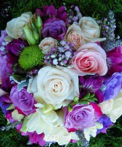Ramo de flores para novia en tonos rosados y morados.