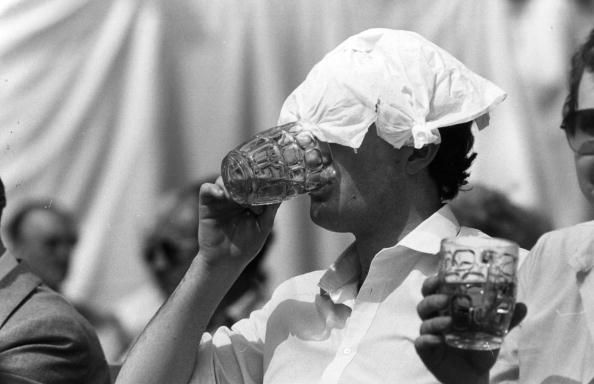 A spectator at the Wimbledon Lawn Tennis Championships enjoys a pint of beer in the hot sun, with a handkerchief on his head.