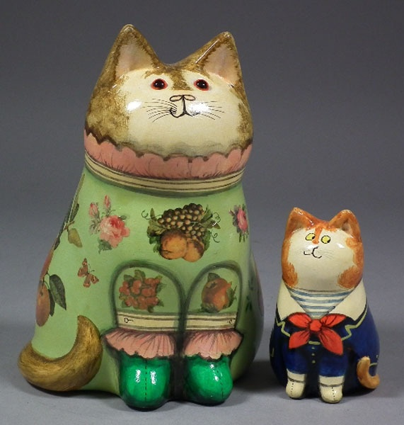 Joan & David De Bethel decorated papier-mâché seated figure of a cat wearing a sailor suit and a ceramic cat wearing green fruit decorated dress